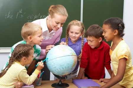 multiracial children: Portrait of pupils looking at globe while listening to teacher during geography lesson