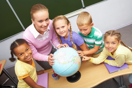 place to learn: Portrait of pupils and teacher looking at camera with globe on table during geography lesson Stock Photo