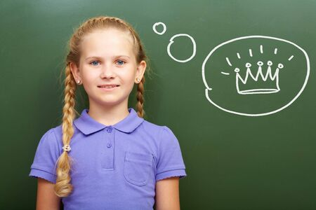 grade: Portrait of smart girl by the blackboard thinking of crown and looking at camera