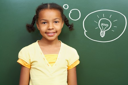 africanamerican: Portrait of smart girl by the blackboard thinking of light idea and looking at camera