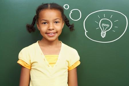 ni�os pensando: Retrato de una chica inteligente por la pizarra pensando en idea luz y mirando la c�mara  Foto de archivo