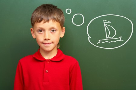 lad: Portrait of smart lad by the blackboard thinking of sail and looking at camera