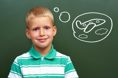 lad: Portrait of smart lad by the blackboard thinking of airplane and looking at camera Stock Photo