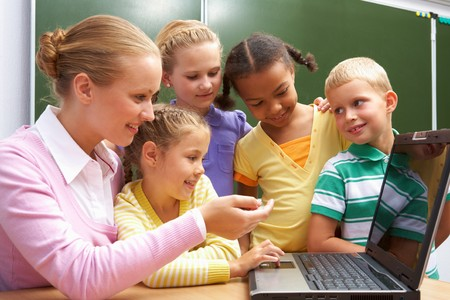 place to learn: Portrait of pupils looking at the laptop while listening to teacher explaining something