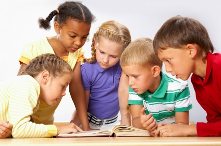 classmate: Portrait of pupils looking at page of encyclopaedia at reading lesson