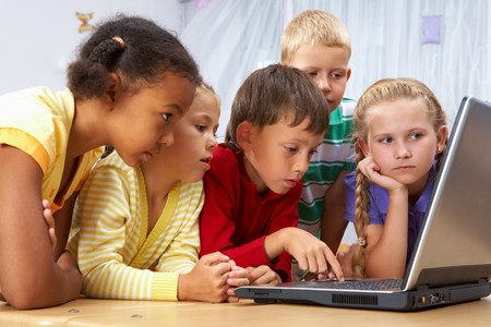 Portrait of smart schoolgirls and schoolboys looking at the laptop  photo