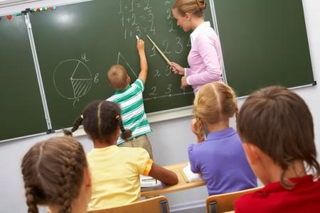 sumas: Foto del estudiante elemental haciendo sumas en la pizarra y mirando mientras su maestro le ayuda a