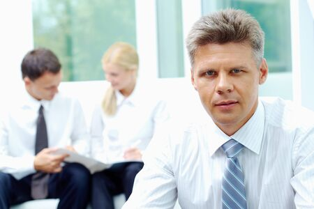 Confident businessman looking at camera at background of his communicating colleagues Stock Photo - 7509010