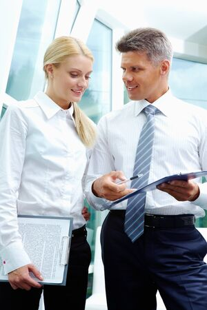 Two smart employees discussing new strategy at meeting photo