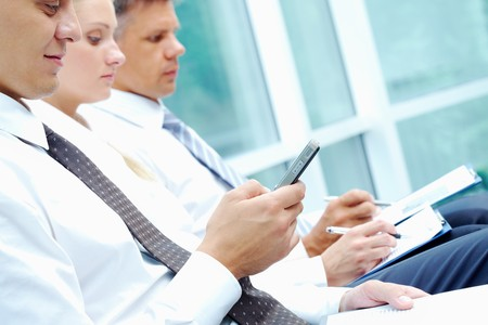 Image of businessman writing sms at conference with working partners on background photo