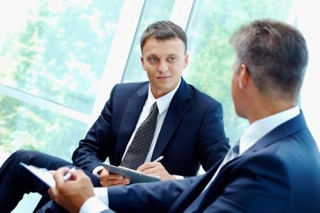 entrevista: Imagen de hombre de negocios inteligente, explicando la nueva estrategia a su compa�ero en reuni�n  Foto de archivo