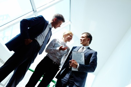 consulting team: Three smart employees discussing new strategy at meeting Stock Photo