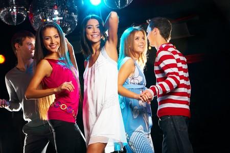 Joyful girls dancing in night club with their friends near by photo