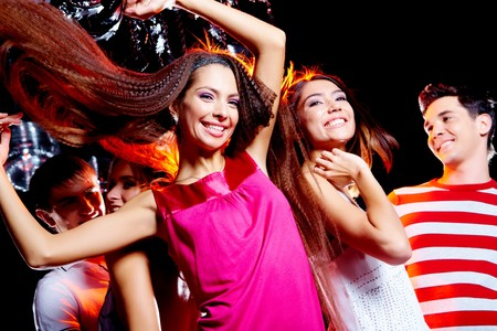 company party: Image of cheerful friends enjoying the party in the night club with joyful girl in front of camera Stock Photo