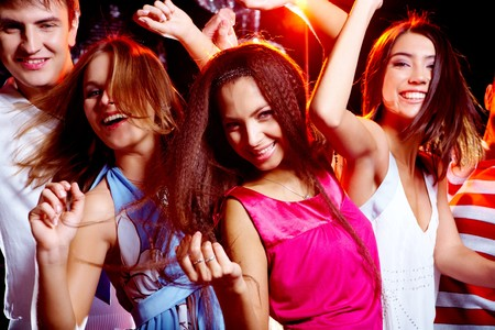 people partying: Portrait of glad teens looking at camera with smiles during disco Stock Photo