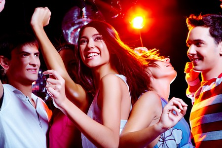 people partying: Photo of energetic girl dancing in the night club with her friends on background