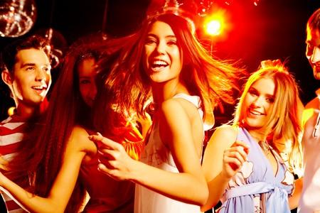 fiestas discoteca: Retrato de ni�a sonriente en vestido blanco bailando entre sus amigos