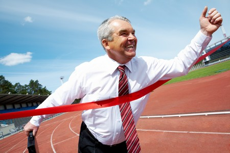Photo of happy mature businessman crossing finish line during race  photo