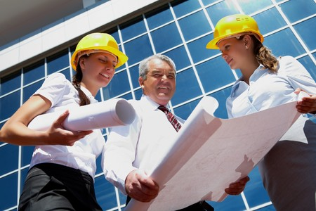 Photo of business partners in helmets on background of modern office building photo