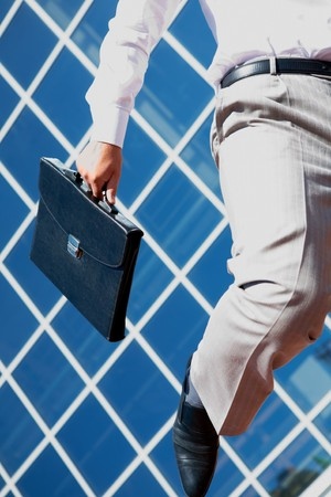 Close-up of businessman with briefcase running photo