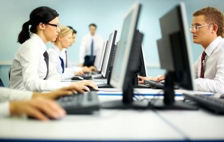 la gente de trabajo: Empresarios sentado en las tablas y mirando sus monitores