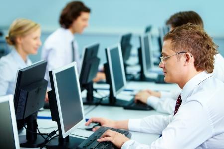 ambiente laboral: Empresarios inteligentes escribiendo en los lugares de trabajo en la sala de inform�tica