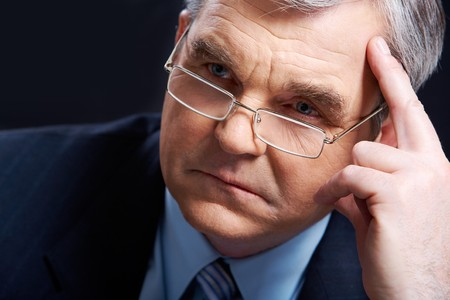 Photo of senior employer thinking about something on black background photo