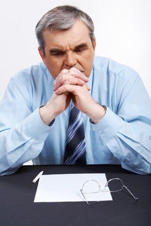 Photo of senior employer thinking about something at workplace photo