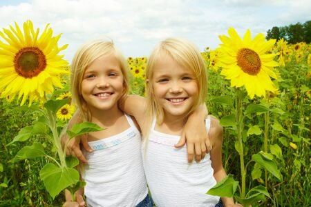 Portrait of cute girls looking at camera and smiling in sunflower field photo