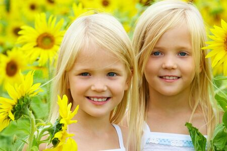 Portrait of cute sisters in sunflower field Stock Photo - 7518045