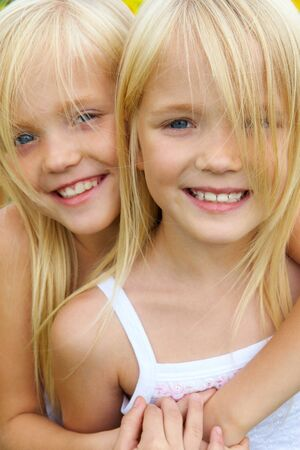 Portrait of cute girl embracing her twin sister and both looking at camera with smiles photo