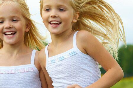 soeur jumelle: Portrait de filles mignonnes ex�cutant et souriant Banque d'images