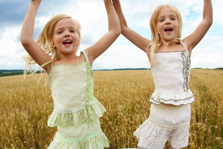 Portrait of energetic twin sisters jumping in wheat field and having fun Stock Photo - 7518032