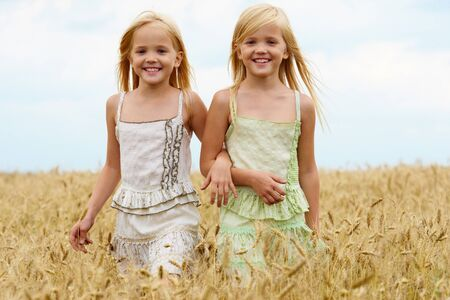 Portrait of cute twins walking down wheat field and smiling photo
