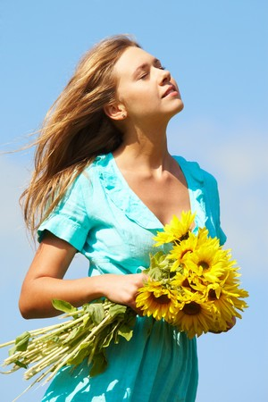 pretty girl with bouquet of sunflowers enjoying summer day photo