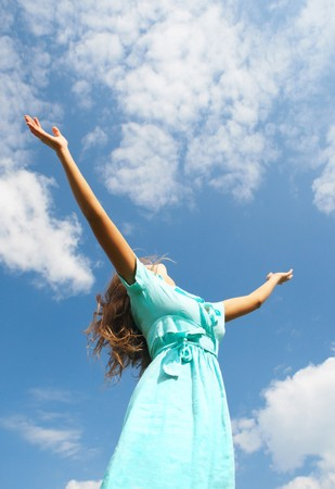 Image of happy female standing with raised arms on summer day Stock Photo