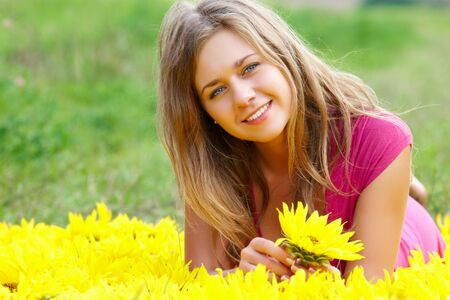 pretty girl with sunflower looking at camera on sunny day photo