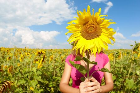 young woman hiding face behind sunflower in meadow Stock Photo - 7518035