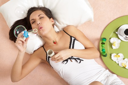 Above view of pretty girl blowing soap bubbles while lying on bed photo