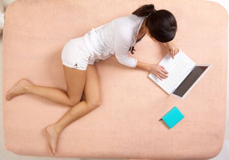 View from above of girl lying on bed and typing on laptop photo
