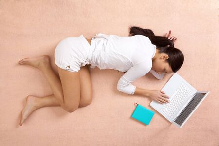 View from above of peaceful girl having a nap with laptop near by photo
