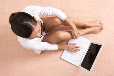 arms above head: View from above of girl sitting and typing on laptop