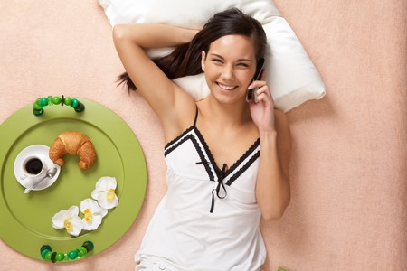 View from above of happy girl speaking on cellular phone on bed photo