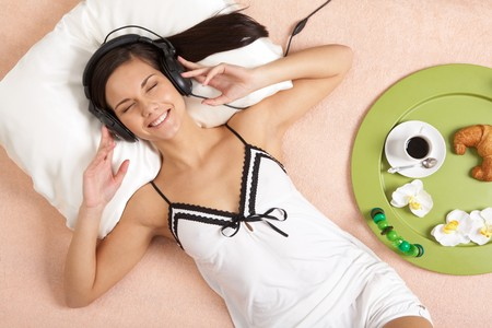 Pretty girl listening to music in headphones and smiling while lying on bed photo