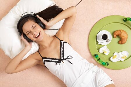 Pretty girl listening to music in headphones and taking pleasure in it photo