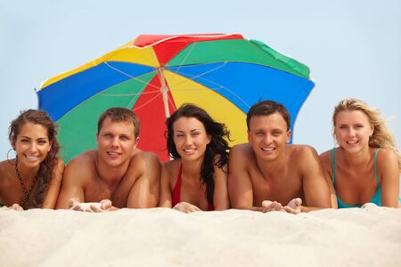 teen beach: Portrait of happy girls and guys lying on sand on summer vacation Stock Photo
