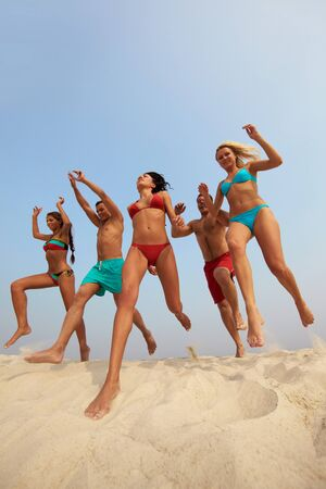 altogether: Portrait of happy friends jumping over sandy shore