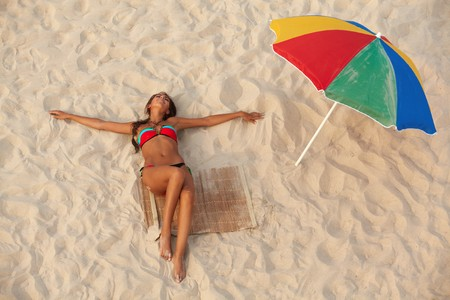 tan woman: pretty girl in swimsuit lying on sandy beach with colorful beach umbrella near by Stock Photo