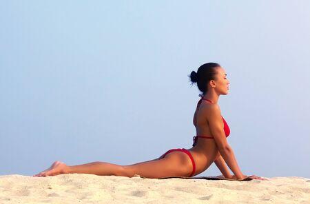 Image of female in red bikini sunbathing on sandy beach during vacation photo