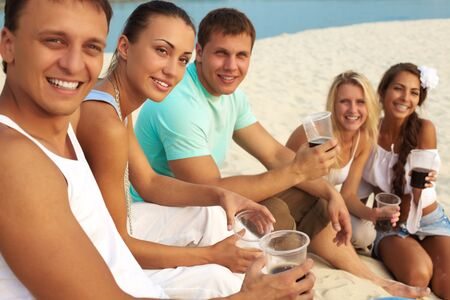 Image of happy friends with drinks having fun at beach party photo